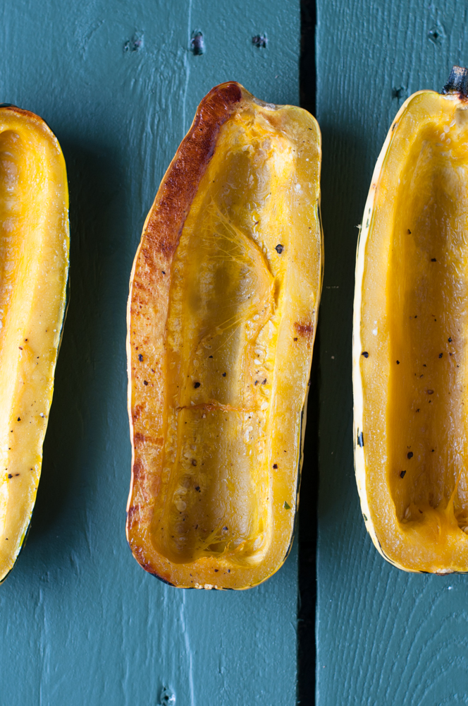 Delicata squash is roasted then stuffed with a fall inspired apple and quinoa stuffing. #fall #vegan