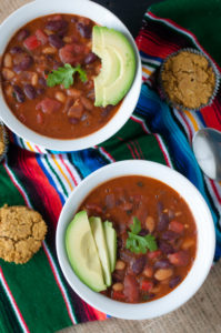 Easy, homemade Vegan Chili that's pantry-friendly. Served with fresh avocado slices and pumpkin cornbread muffins. The perfect cozy, fall dinner!