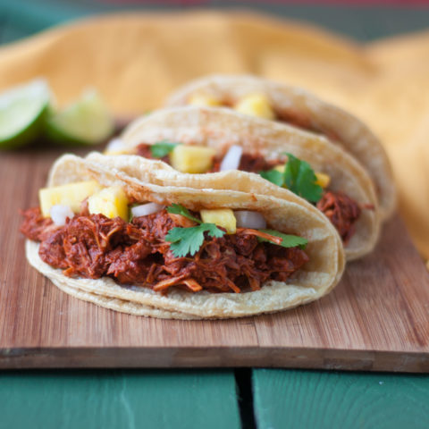 Slow Cooker Jackfruit Adobada Tacos. Jackfruit is slow cooked in a well balanced chile and citrus sauce along with pineapple. Perfect for Taco Tuesday! #vegan #tacos
