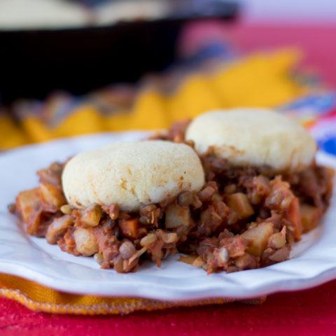 Lentil Picadillo topped with light, tender arepa patties. A warm, cozy casserole. #vegan #glutenfree