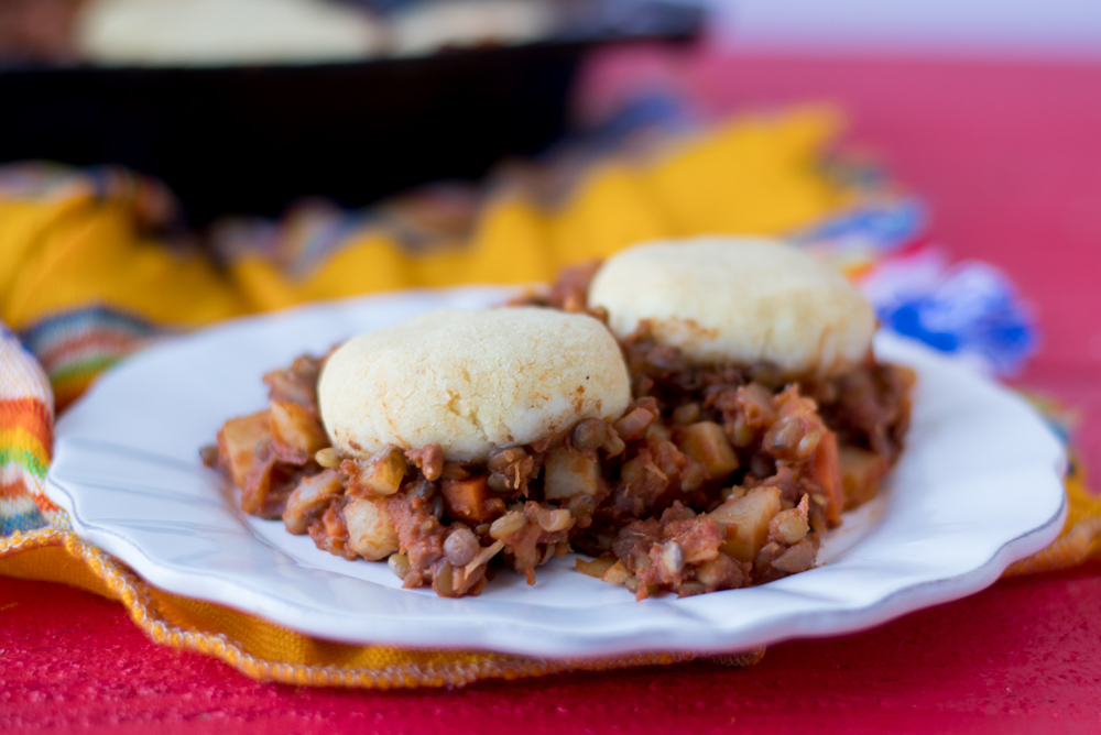 Lentil Picadillo topped with light, tender arepa patties. A warm, cozy casserole. #vegan #glutenfree