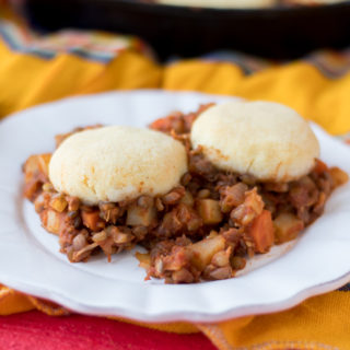 Warm, homey vegan + gluten-free casserole. Lentil Picadillo is topped with light, fluffy arepa biscuits.