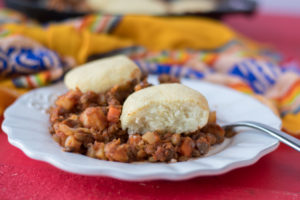 Warm, homey vegan and gluten-free casserole. Lentil picadillo is topped with light, tender arepa biscuit toppings.