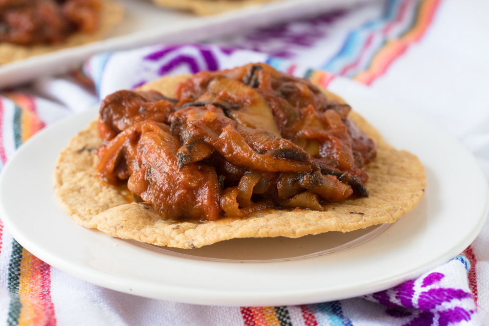 Mushroom Tinga Tostadas: a vegan take on a classic Mexican recipe. Meaty, mushroom are cooked in a flavorful tomato and chipotle sauce and served on corn tostadas. So good!