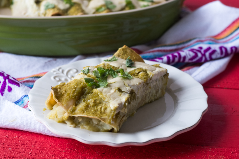 These Potato and Roasted Enchiladas are inspired by Mexican papas con rajas. The combination of the potatoes with the spicy poblanos is so good! #vegan #mexican