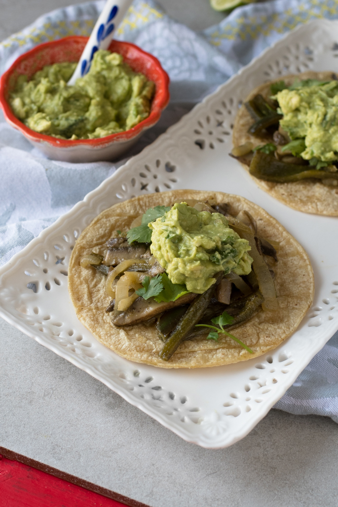 Portobella mushroom and poblano pepper fajitas topped with a simple homemade guacamole.