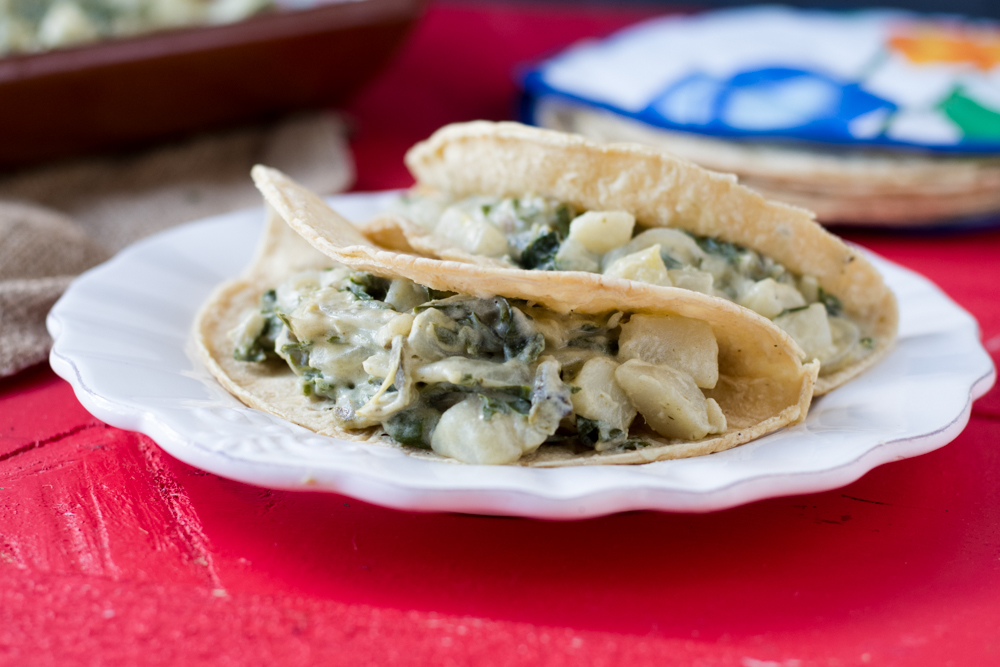 Rich, creamy braised swiss chard and potato tacos. The combination of chile peppers and the crema is so good!