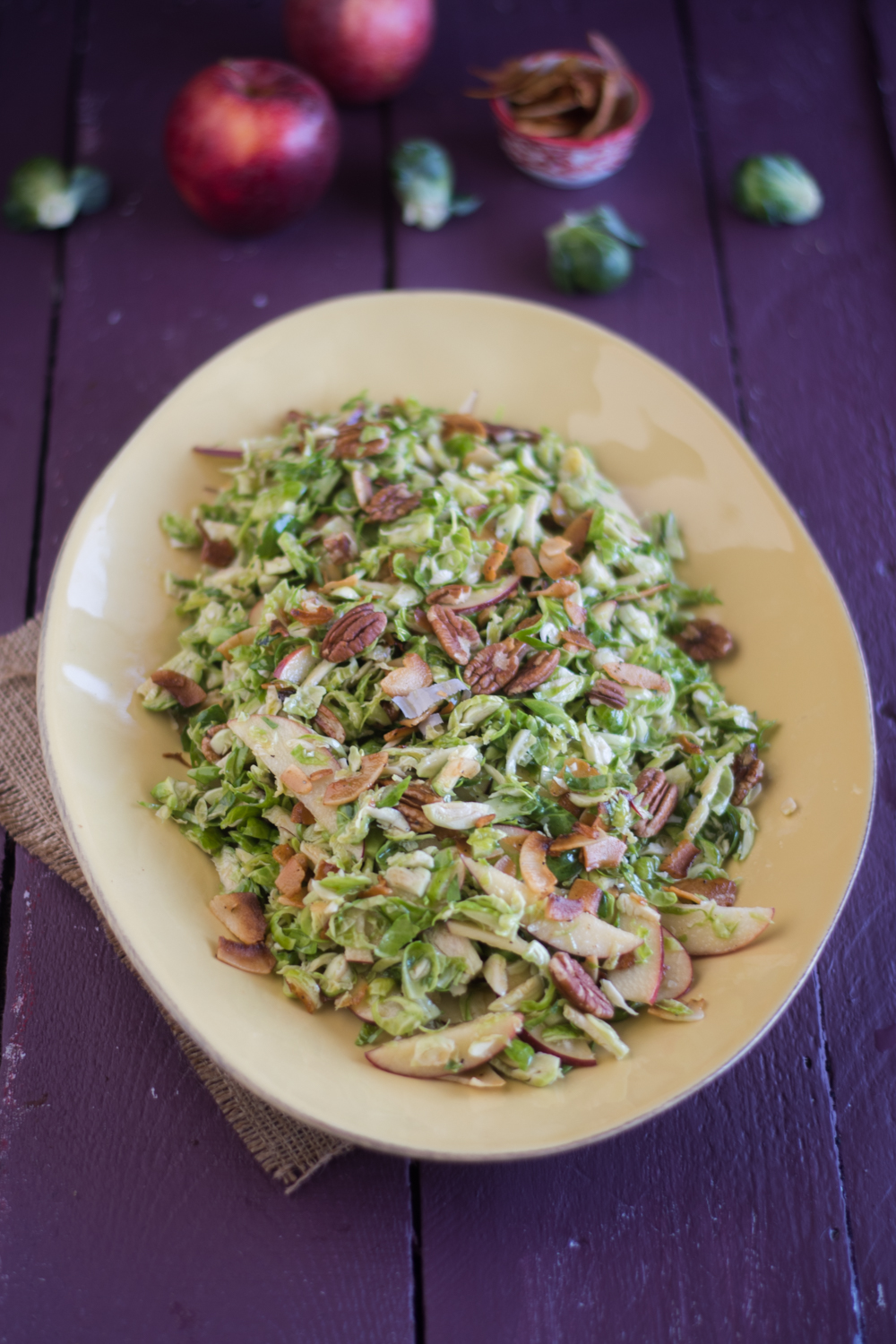 Fall inspired brussel sprout and apple salad with a maple dressing. The salad is elevated with coconut bacon!