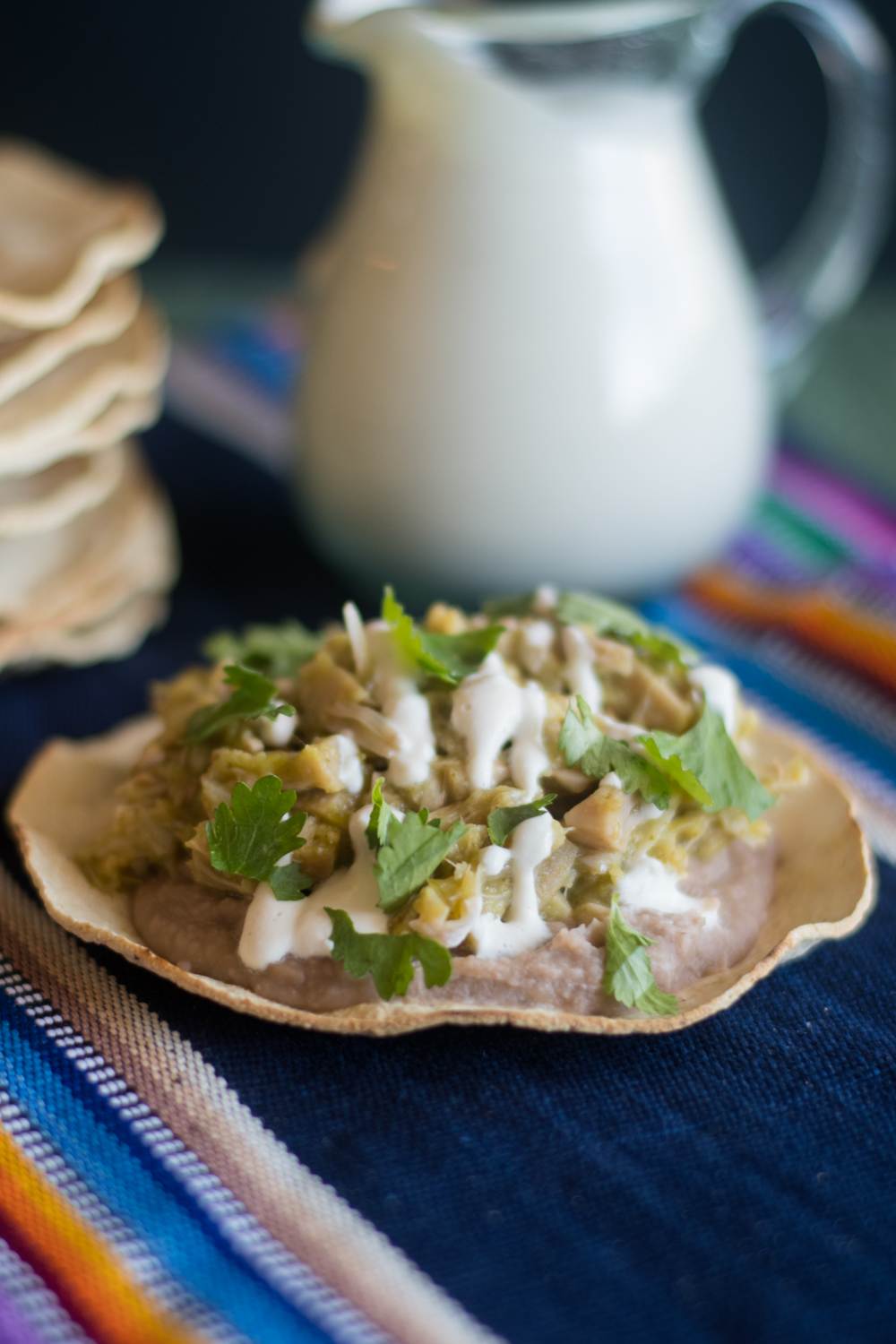 Tostadas are topped with refried beans, jackfruit cooked in salsa verde, and cashew crema. Perfect way to switch up taco night!