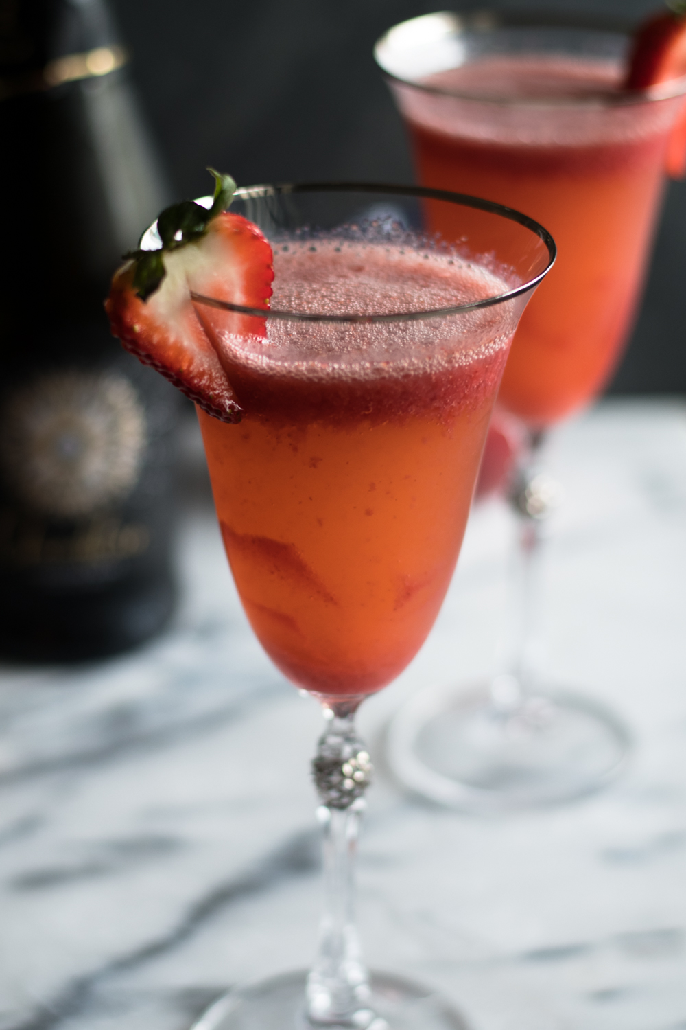 Strawberry Bellini is a twist on the classic peach bellini which is made with peach puree and sparkling wine. Instead of using peach puree, this cocktail uses a strawberry puree. #cocktail #wine #summer #recipe #strawberry