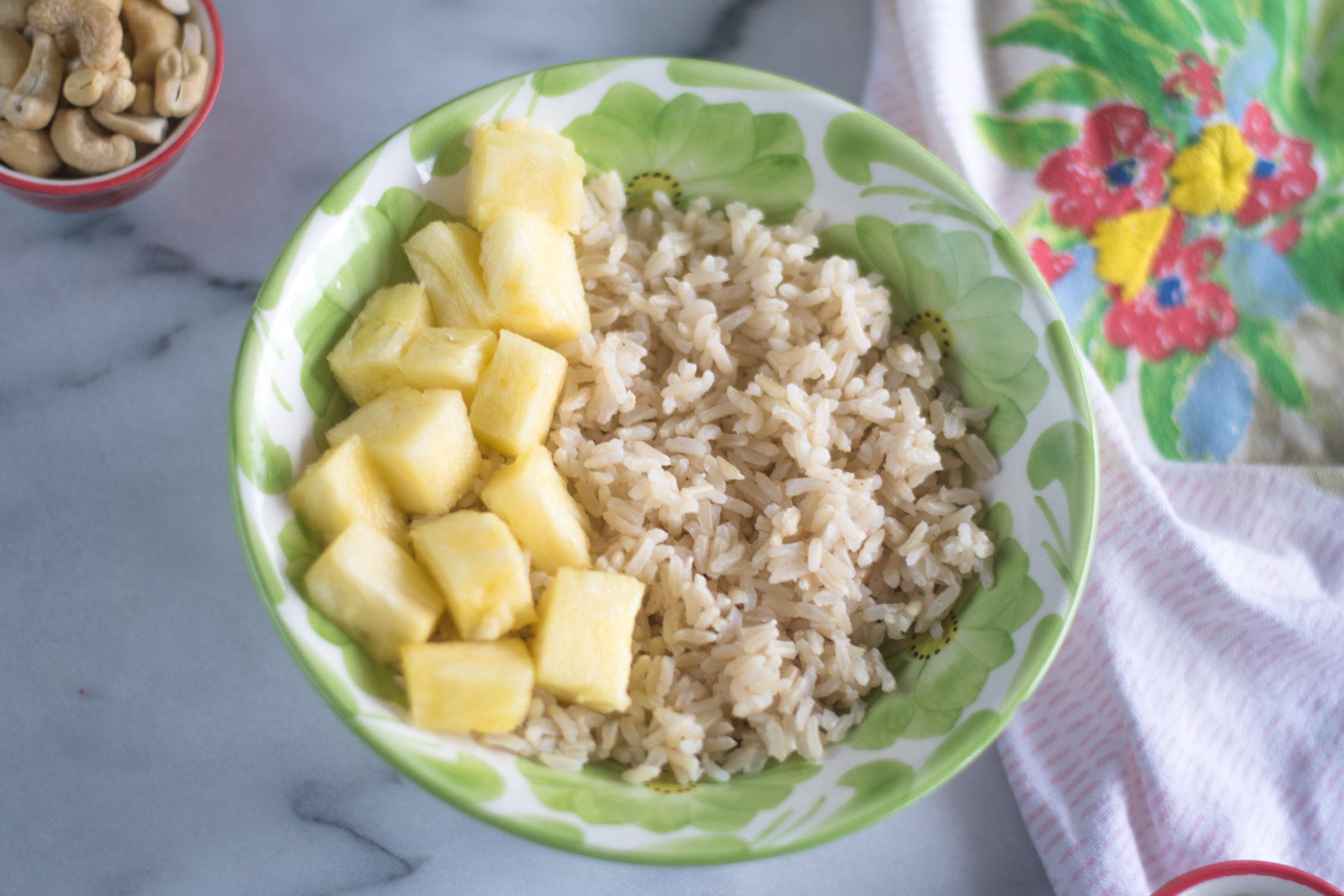 A Touch of the Tropics Rice Bowl starts by adding cooked jasmine rice to a bowl. The rice is topped with fresh pineapple, cashews, roasted sweet potatoes, and hemp seeds.