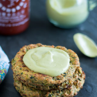 Vegan Zucchini Fritters topped with an avocado crema.