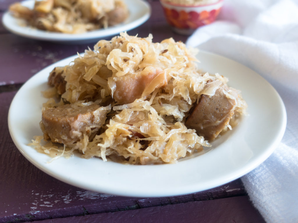 This Vegan Sauerkraut and Bratwurst Casserole is a cozy casserole that is perfect for the cooler weather. It is loaded with vegan bratwurst sausages, onion, apples, and lots of sauerkraut!  #vegan #casserole #sausages #food #dinner