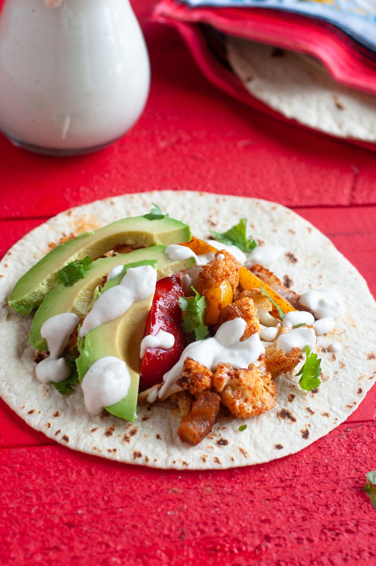 Looking for a quick and easy dinner recipe? You're going to love how easy it is to make these Vegan Sheet Pan Cauliflower Fajitas! #vegan #fajitas #vegetarian #dinner #sheetpan #easyrecipes