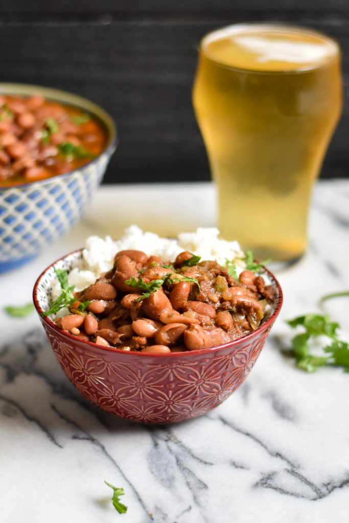 Pinto beans are cooked in a flavorful broth of beer and spices. The Instant Pot makes cooking beans so easy! #beans #Mexican #vegan #frijoles #VeganMexican