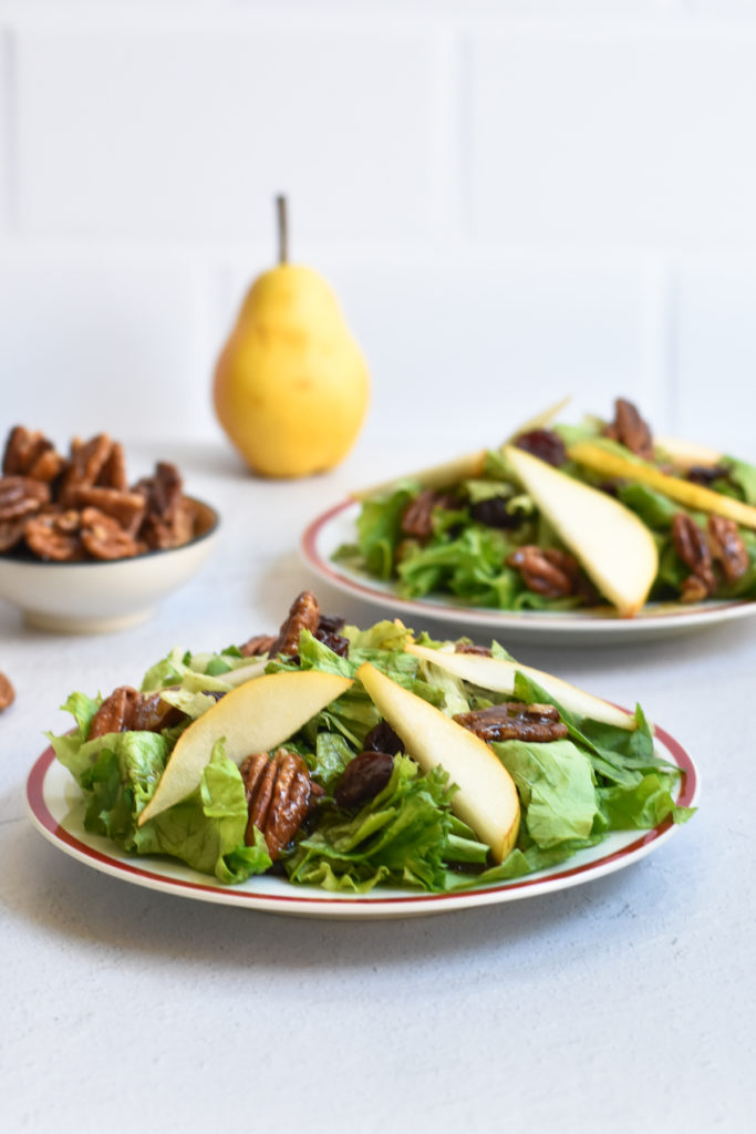 This fall inspired pear salad with candied pecans and balsamic vinaigrette is slightly sweet, tart and perfect for fall entertaining. #salad #pear #holiday #recipes #vegan #vegetarian #dressing #pecans #Thanksgiving #Christmas