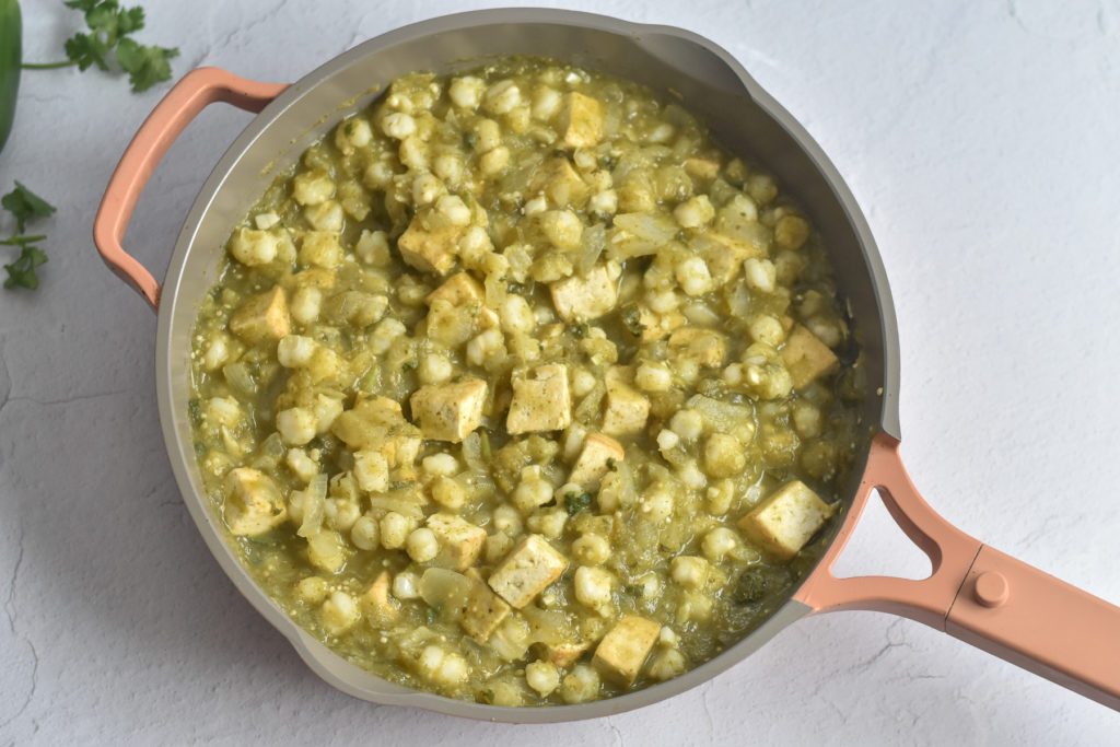 Tofu is braised in salsa verde. Hominy adds a great texture and bulks up this comforting stew.