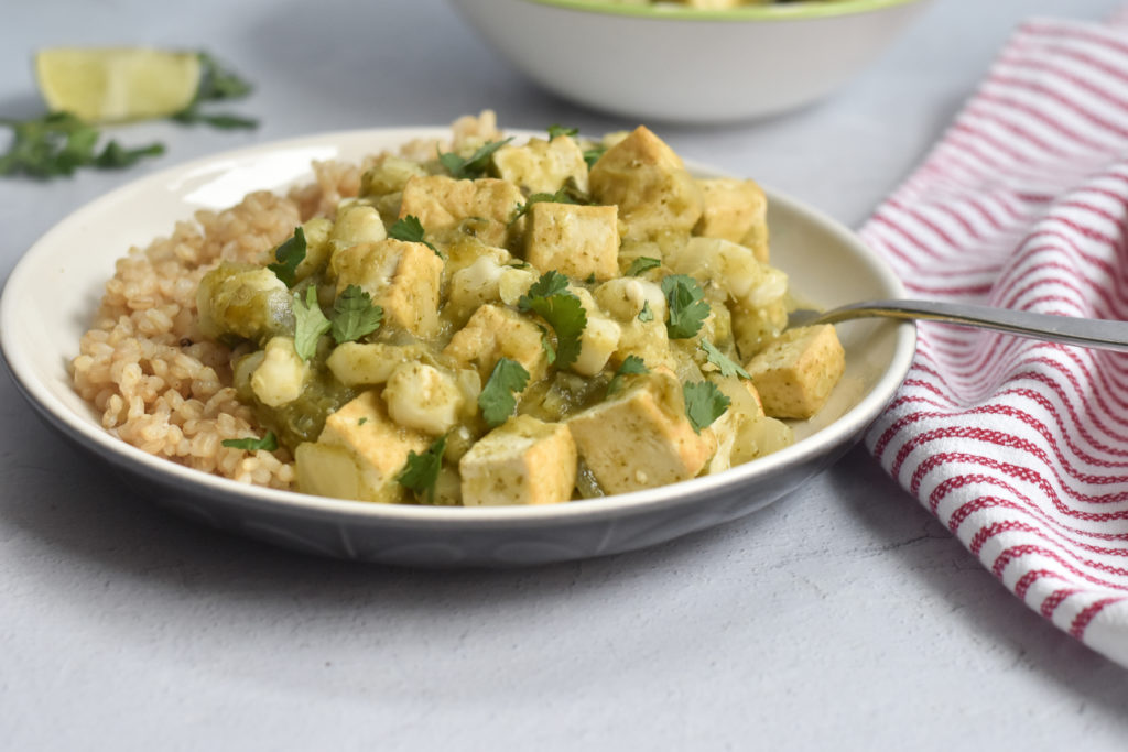 Hearty, comforting with a spicy kick, this recipe for Braised Tofu with Hominy is a flavorful plant-based dinner!