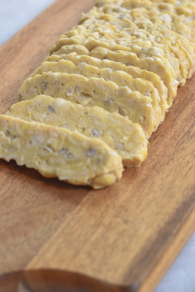 Tempeh is a soy-based plant-based protein source that originated in Indonesia. It is made by fermenting cooked soybeans and then forming the mixture into a firm, dense cake.