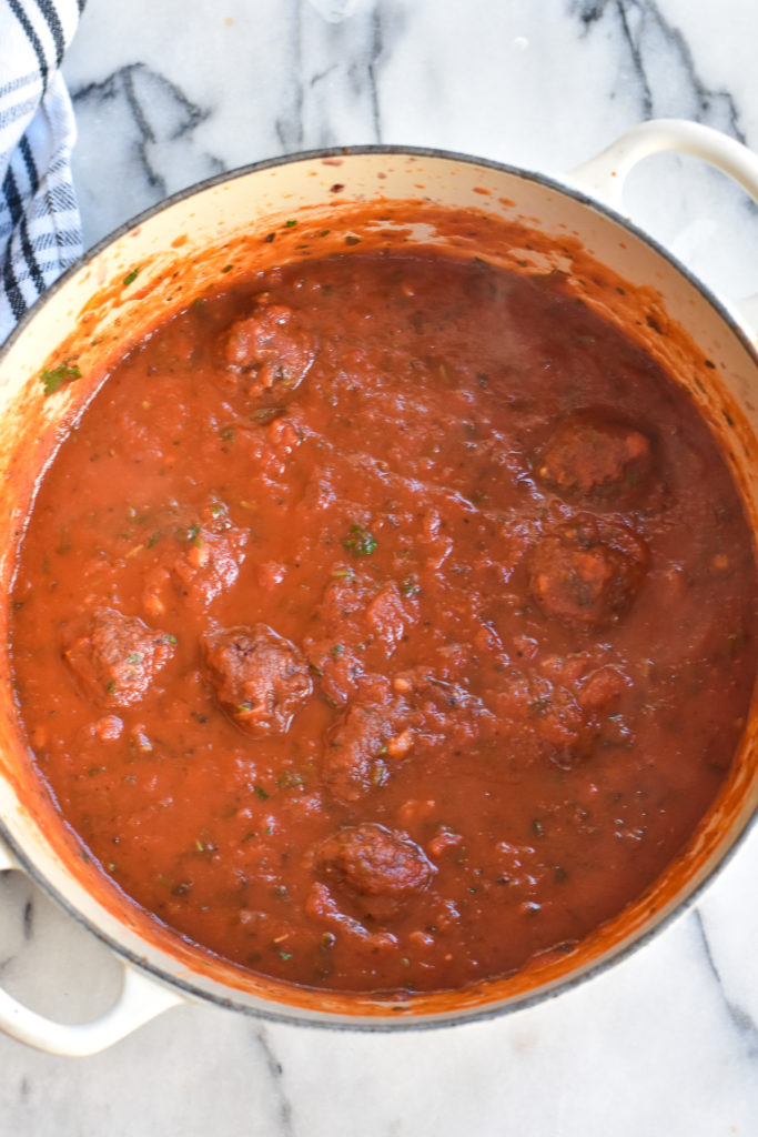 Cooking marinara sauce with meatballs.
