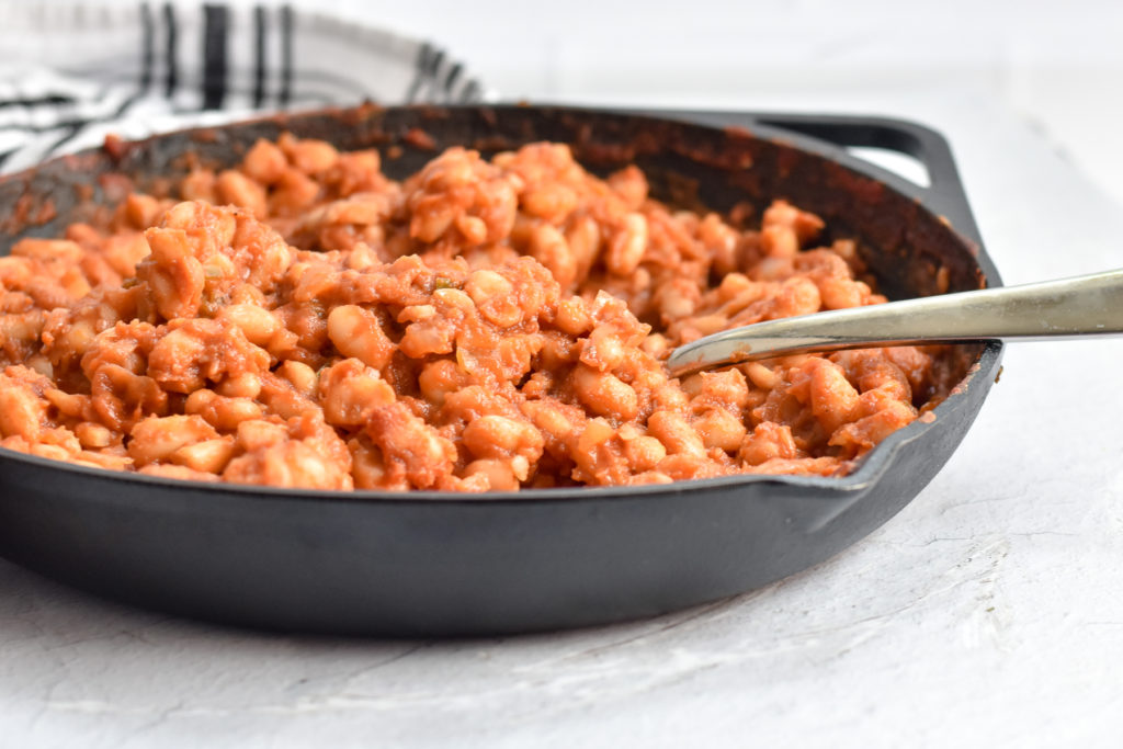 Baked beans cooked in a cast iron skillet on the grill.